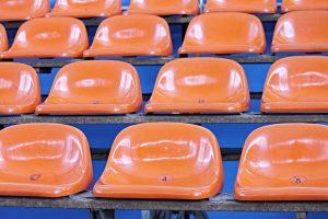 Orange Sitzflächen aus Kunststoff in einem Stadium