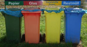 Vier Mülleimer in grün, rot, gelb und blau mit den Überschriften Papier, Glas, Kunstoffe Dosen und Restmüll